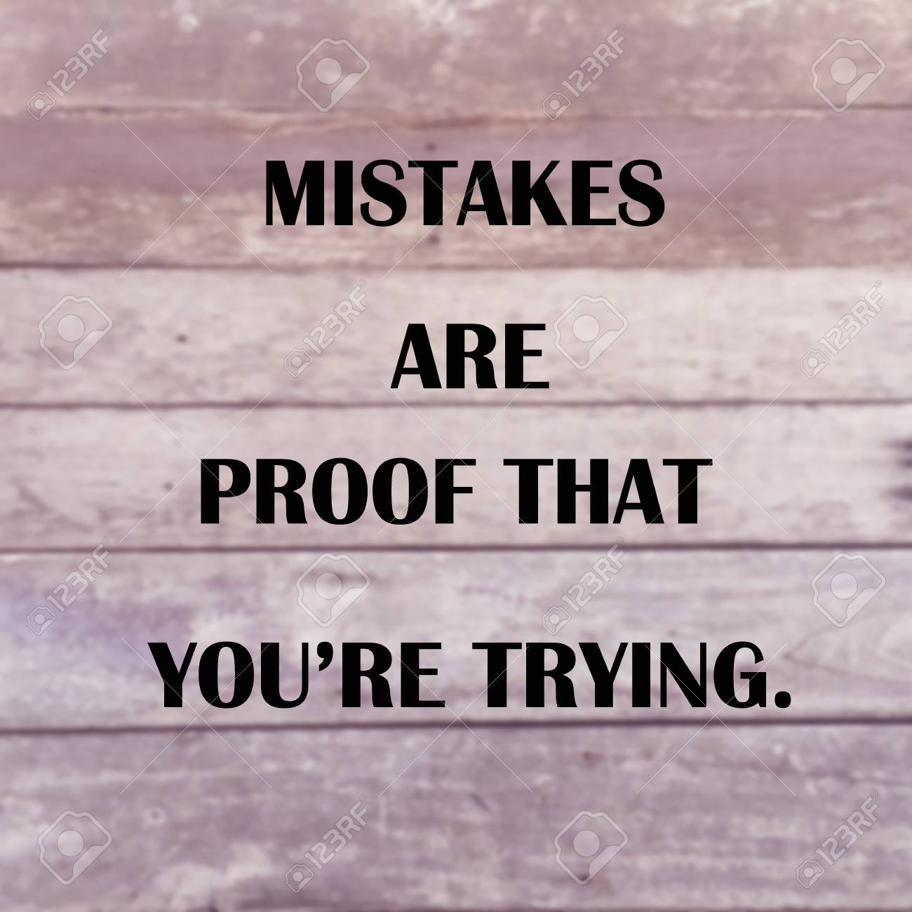 "Inspirational quote ""mistakes are proof that you're trying"" on blurred wood planks background"